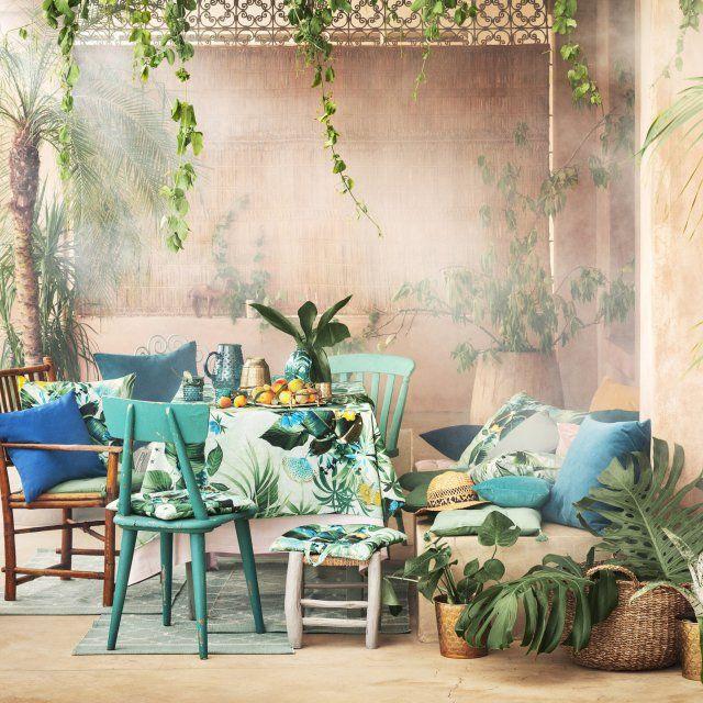 Une salle à manger exotique avec des meubles en bois brut ou peint et du linge au motif tropical comme la nappe Summer ou les coussins Summer
