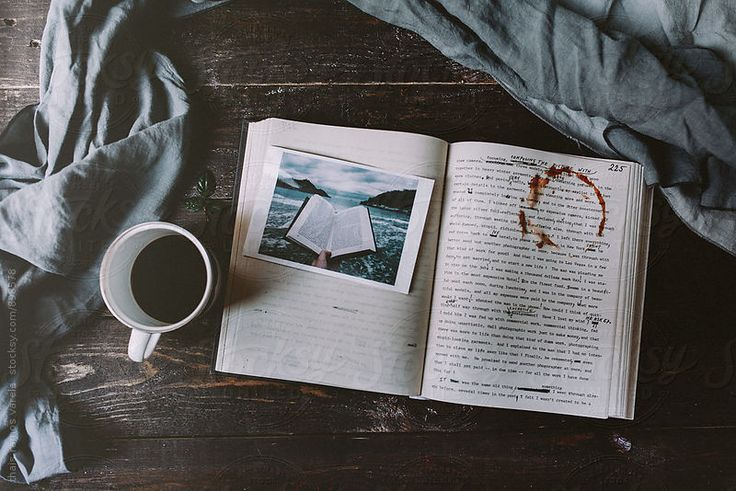 a cup of coffee in a wood table with a photography over an open book