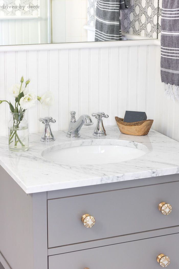Gray vanity with marble vanity top and Delta Cassidy chrome faucet