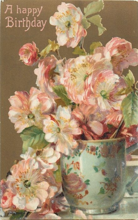 A HAPPY BIRTHDAY  patterned vase of blossoms which overflow onto table, brown background