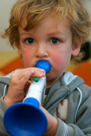Young boy blowing a toy trumpet