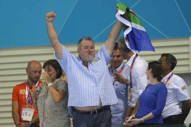 Proud papa: Dad Bert le Clos hold the South African flag as son Chad swims to victory