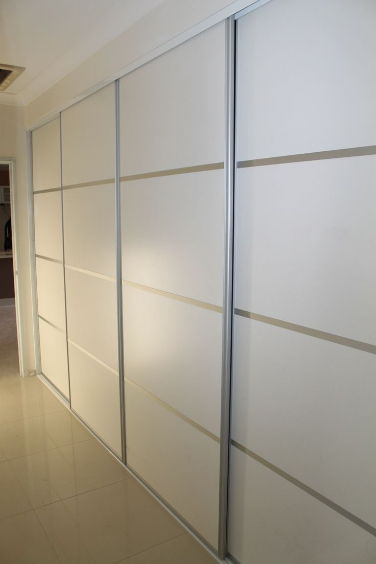 "Sliding 4 panel doors for an extra wide  hallway cupboard. .  The panel is white melamine in a ""sheen"" finish with clear anodised aluminium frames. The four panel doors break up what would have been a very dull area if single panel doors had been used. The horizontal lines accentuate the width of the room creating a feeling of more space.  www.formfunctionnt.com.au"