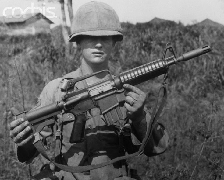 An American soldier presents his early Colt Automatic Rifle-15 (CAR-15) XM177E1 Commando Model 609 for a snapshot in Vietnam, via Corbis. Note its telescoping rear stock, round forestock, forward-assist, shorter barrel, heavier flash suppressor, and lack of an ejected case deflector. The CAR-15 military weapons system was a family of the AR-15 and M16 rifles marketed by Colt in the late 1960s and early 1970s.