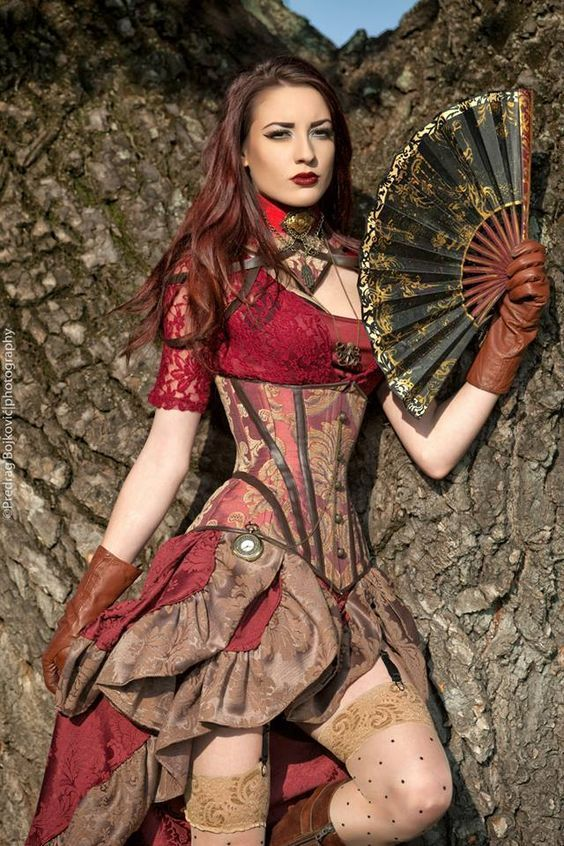 Steampunk in Burgundy Brocade (red lace blouse, tan and burgundy brocade underbust corset with matching skirt, polka dot thigh high stockings, brown gloves, necklaces, pocket watch and collar, and folding fan - For costume tutorials, clothing guide, fashion inspiration photo gallery, calendar of Steampunk events, & more, visit http://SteampunkFashionGuide.com