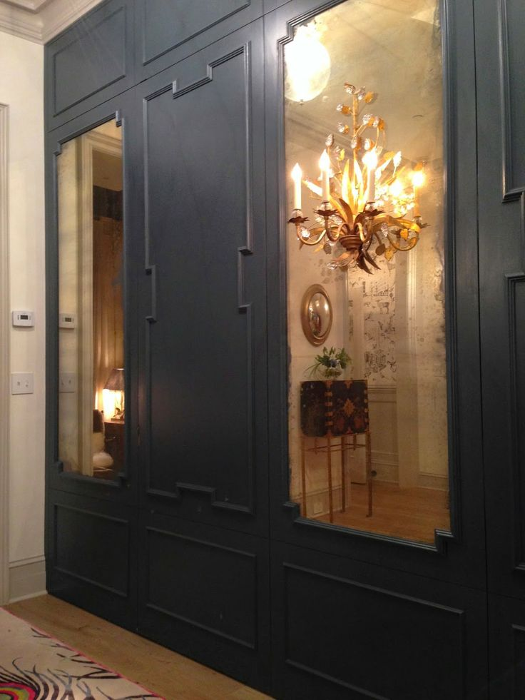 This wall with antique mirrors hides a closet on the left and a powder room on the right behind jib doors.
