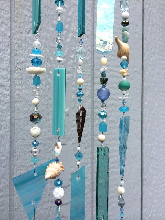 Sea shells from the Northern California beaches add a special touch to this stained glass sun catcher / wind chime. Turquoise and blue stained glass and glass beads complement the beauty of the sea shells to give a calm and elegant piece of art for your home. A variety of glass beads and crystals along with some semi-precious beads add sparkle that will catch the suns rays. This is a beautiful ocean themed sun catcher!    Each piece of stained glass has its own individual shape and color...
