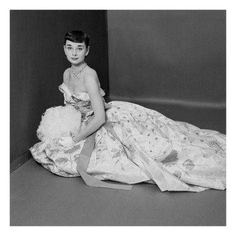 Vogue - March 1952 by Richard Rutledge. In this outtake from a Vogue photo shoot, actress Audrey Hepburn gazes serenely at the camera. She wears a strapless ball gown made of Bianchini flowered silk taffeta, which was designed by the famed Adrian. This quintessential Hepburn image is undermined by the rather informal setting, which makes this image even more of an intimate look into her fabled life. This black and white portrait of the actress was created by noted photographer Richard…