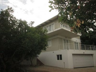 This Contemporary , trendy self-catering holiday house is situated in popular Sandbaai , Hermanus. Ichaboe's layout sleeps 12 with 5 bedrooms and 3 bathrooms designed for easy entertainment and a relaxing break-away from the everyday normality.   Within walking distance to the local Sandbaai beach with only a greenbelt of milkwood trees between you and the ocean. Providing a large outdoor patio and braai area leading off the open plan kitchen , lounge and dining area.
