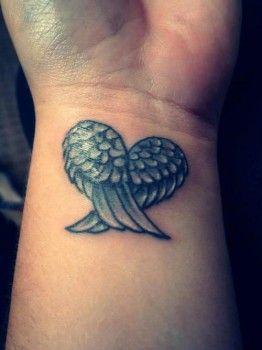 Un corazón conformado por un par de alas tatuado en la muñeca de una mujer. Las plumas son de color blanco con sombreado gris.