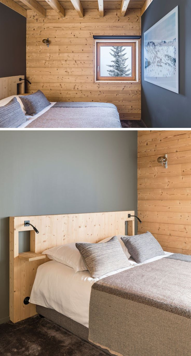 This rustic modern bedroom features dark grey accent walls, a custom wood headboard, and a square window with mountain views. | modern cabin, cozy room