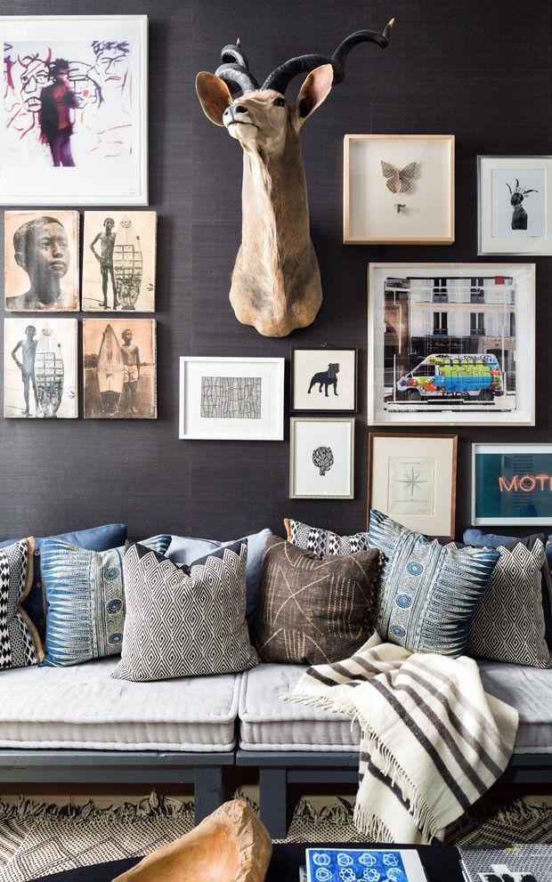 Sala de estar tem futon e almofadas de diferentes estampas. Quadros e fotografias diversas
