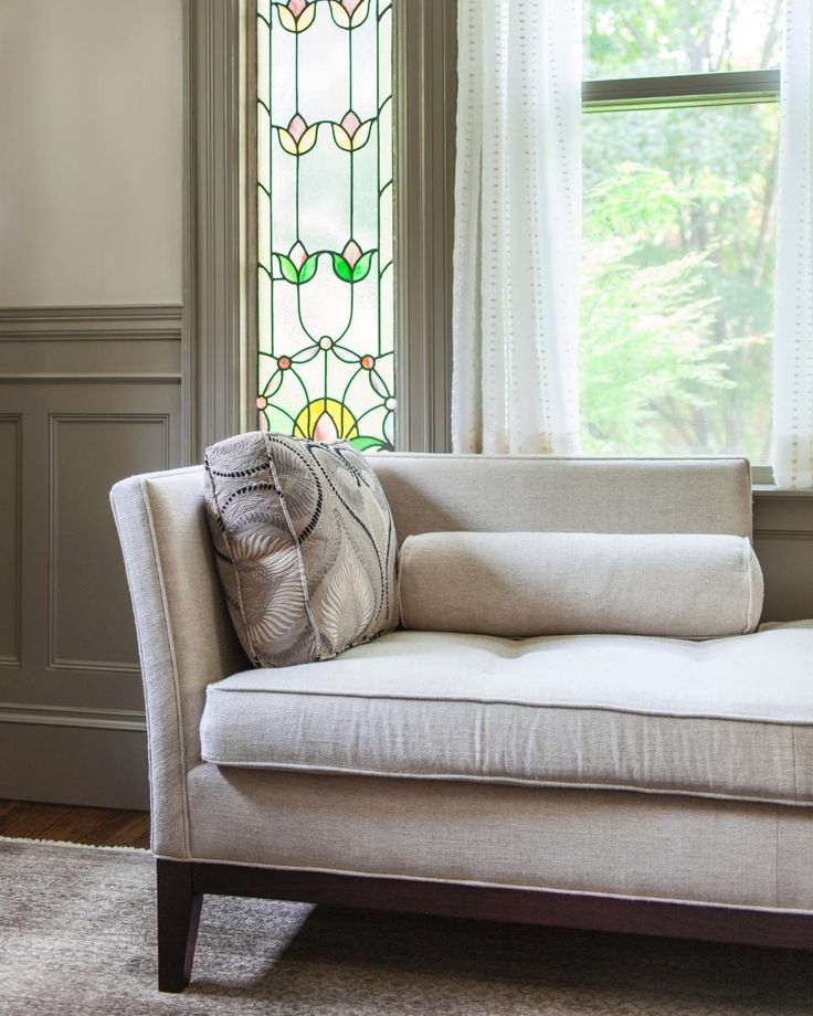 A clean-lined chaise lounge backs up to a window flanked with gorgeous stained glass panels in this neutral family room. The pairing creates an interesting juxtaposition of styles, achieving a transitional look that's classy and timeless.
