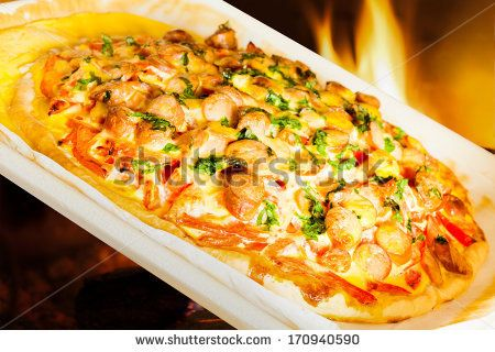 Closeup of pizza with potatoes, tomatoes and wurst, on fireplace background.