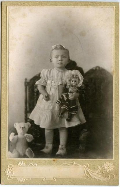Antique photo of a little girl with her doll and Teddy bear, circa 1900.