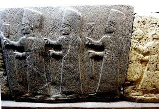 Cerimônia Religiosa Escultura em pedra calcária neo-Hitita. Trés mulheres caminhando cobertas por longas vestes e altos chapéus. Acredita-se que devem ser sacerdotisas da deusa Kubaba. Cada uma segura um feixe de cereais na mão direita e um cetro na mão esquerda.