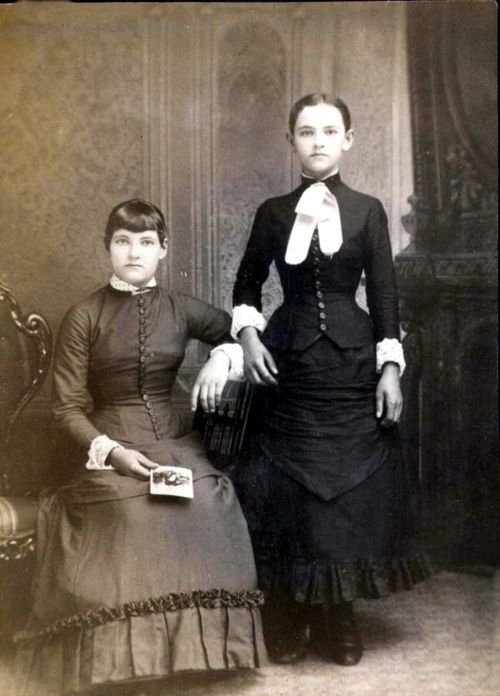 The girl who is standing in the photo is the one who is dead. This is a classic example of photographic art. Notice the hands.   For people wondering how the corpse is standing up, there is a posing stand supporting the body it's very hard to see but the stand is supporting the neck, arms and back.