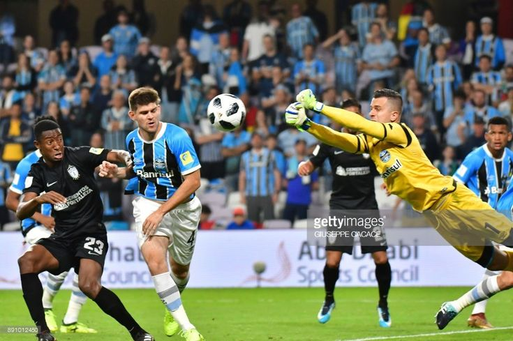 Gremio FBPA's goalkeeper Marcelo Grohe (R) of Brasil saves a ball as his teammate Walter Kannemann (2L) and CF Pachuca's Oscar Murillo (L) react during the first semi-final of the FIFA Club World Cup UAE 2017 between Gremio FBPA and CF Pachuca at the Hazza Bin Zayed Stadium on December 12, 2017 in Al-Ain. /