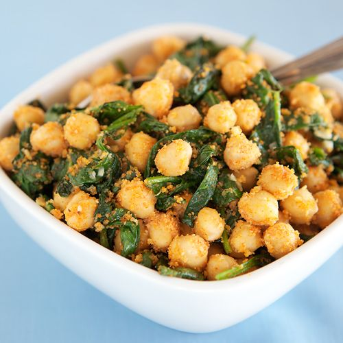 2 tsp olive oil  18 oz fresh baby spinach  1 clove garlic, minced  1 15-oz can chickpeas, drained and rinsed (NOTE: Opt for BPA-free cans, such as Eden Organics)  2 tbsp dry whole-wheat bread crumbs  1/2 tsp sweet paprika  1/4 tsp ground cumin  1/4 tsp sea salt  Fresh ground black pepper, to taste  1 tsp red wine vinegar
