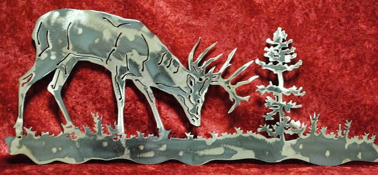 """Deer with tree landscape. This majestic deer will welcome you home as he stands grazing by a tree, still alert to the world around him. The item picture is done in our regular grind finish allowing each one to be unique. Wall Decor Approximate Size: 8.5"""" x 19.5"""" Weight of item: 1 lbs 7 oz Material: Handcrafted out of 14 gauge steel using a CNC machine with a plasma cutter, providing incredible detail. Edges are sharp: tips of antlers. Finish: To get a blue finish we heat up the surface of..."""