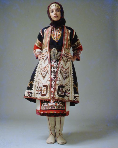 "The older bridal version of the Makra Gefyra (Zaloufi), Thrace. The festive dress with its embroidered overcoat known by the name of ""terliki"". A special effect is created by the white felt boots. Early 20th century. Peloponnesian Folklore Foundation, Nafplion, Greece."
