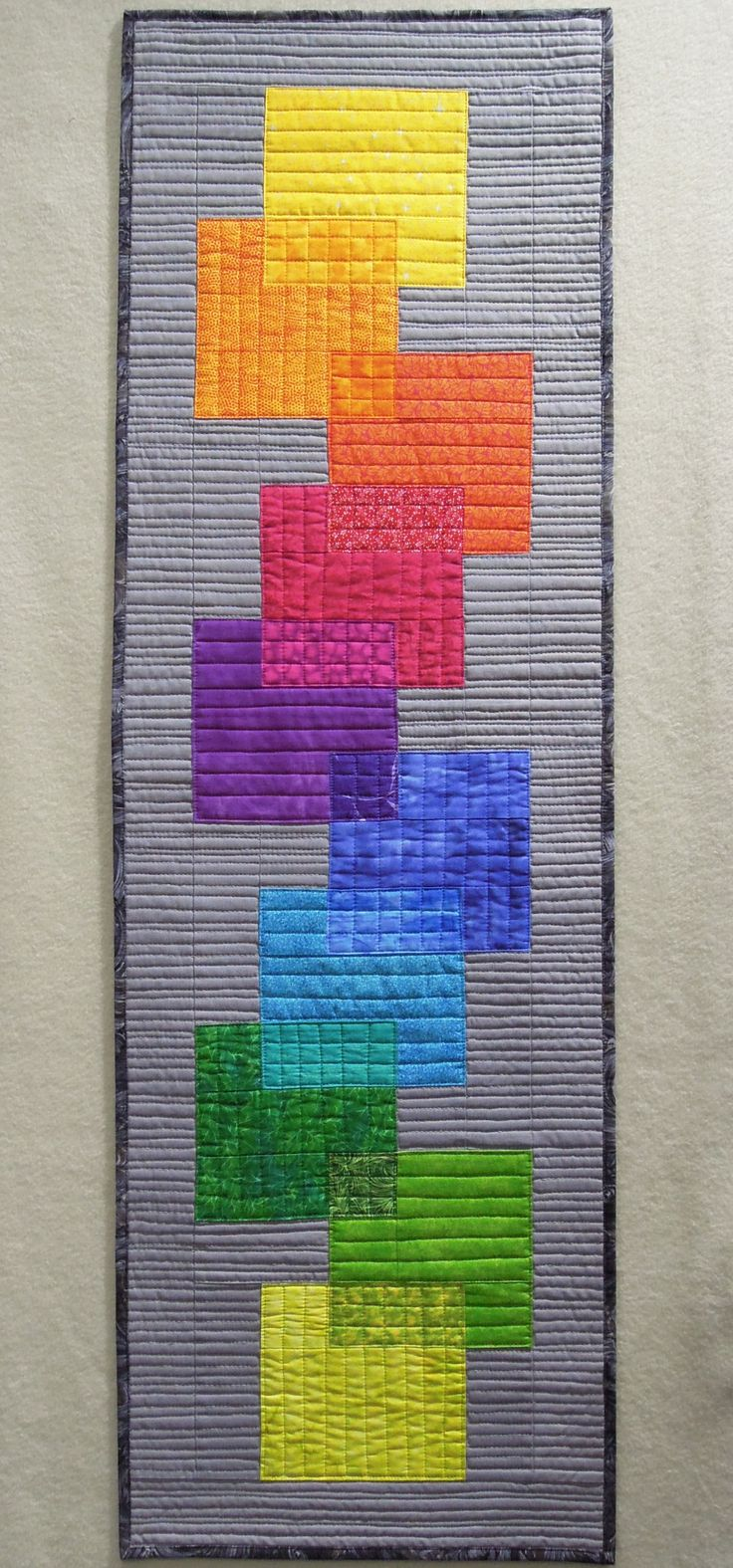 Rainbow Transparency Skinny Quilt. Techniques used: machine piecing; illusion of transparency. Machine pieced and quilted. Finished size: 14.25″ by 45″. The selection of the fabrics create the illusion of transparency, but in actuality the fabrics are all pieced – there is no actual overlapping of fabrics. I used a solid medium gray for the background, and a mottled gray-charcoal-black for the binding. The background was quilted with free-motion organic, mostly straight lines.