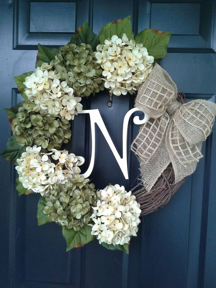 The Olivia wreath will make a beautiful addition to your front door. It has sage and cream hydrangeas attached to a grapevine wreath and tied with a burlap and burlap net bow. Monogram letter is pictured in cream... Choose the initial monogram you would like to make it personal. Measures approximately 20 in diameter.  Each flower, bow and letter is wired and glued to the wreath for optimum durability