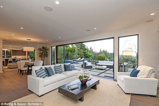 He can fit plenty of pals in here: The living room is spacious with floor to ceiling windo...