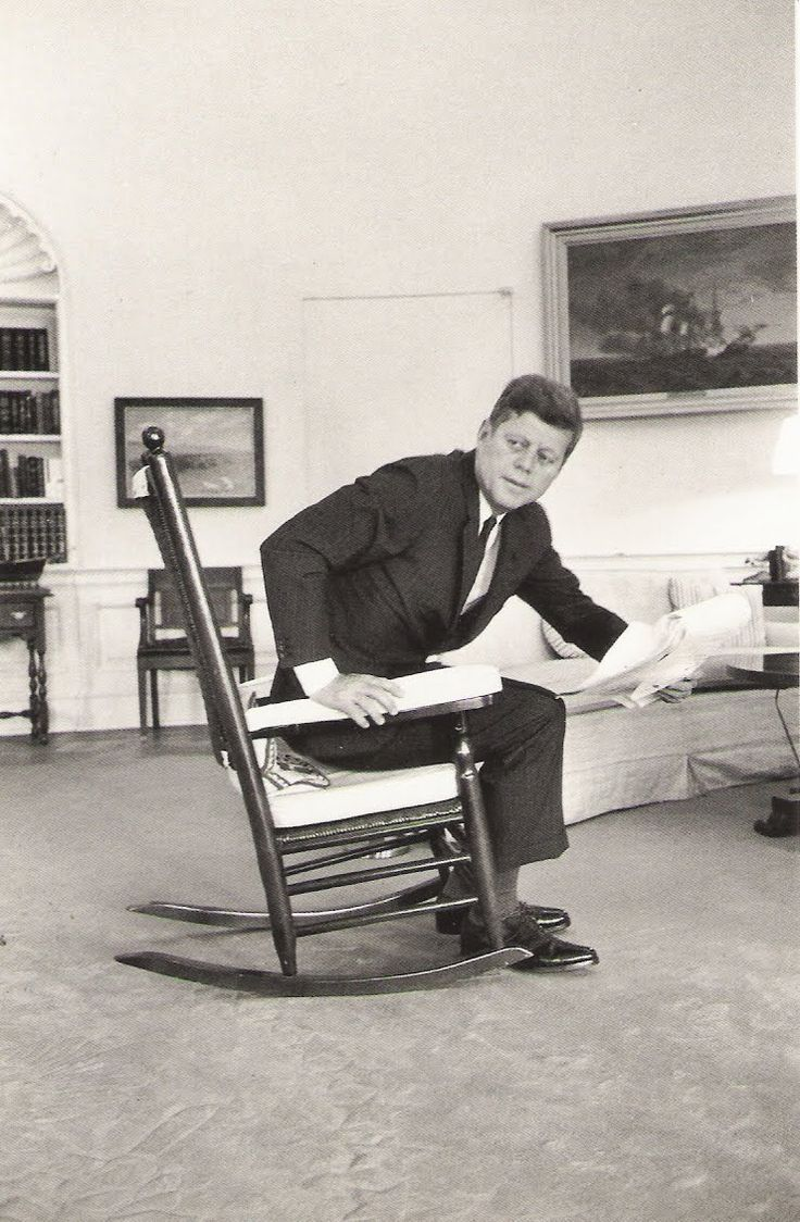 , President John F. Kennedy rises from his favorite rocking chair ...