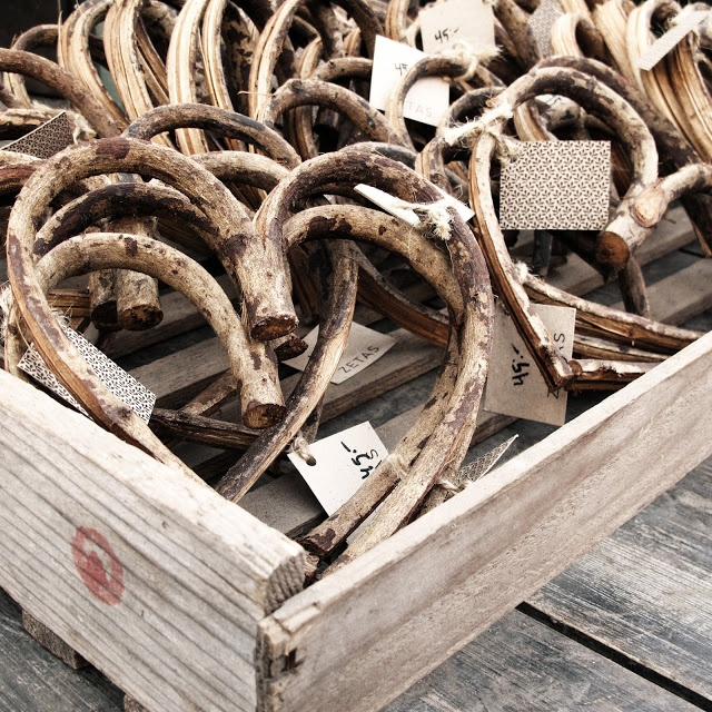 A wooden crate of hearts created from bending branches and then dried and aged.