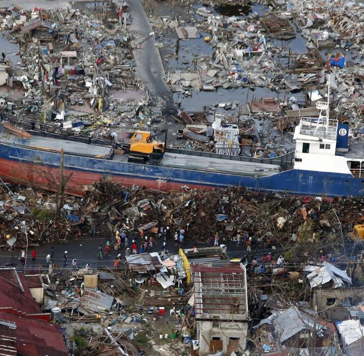 Residents look at a ship that was swept by Typhoon Haiyan nearly two weeks ago, in downtown Tacloban city