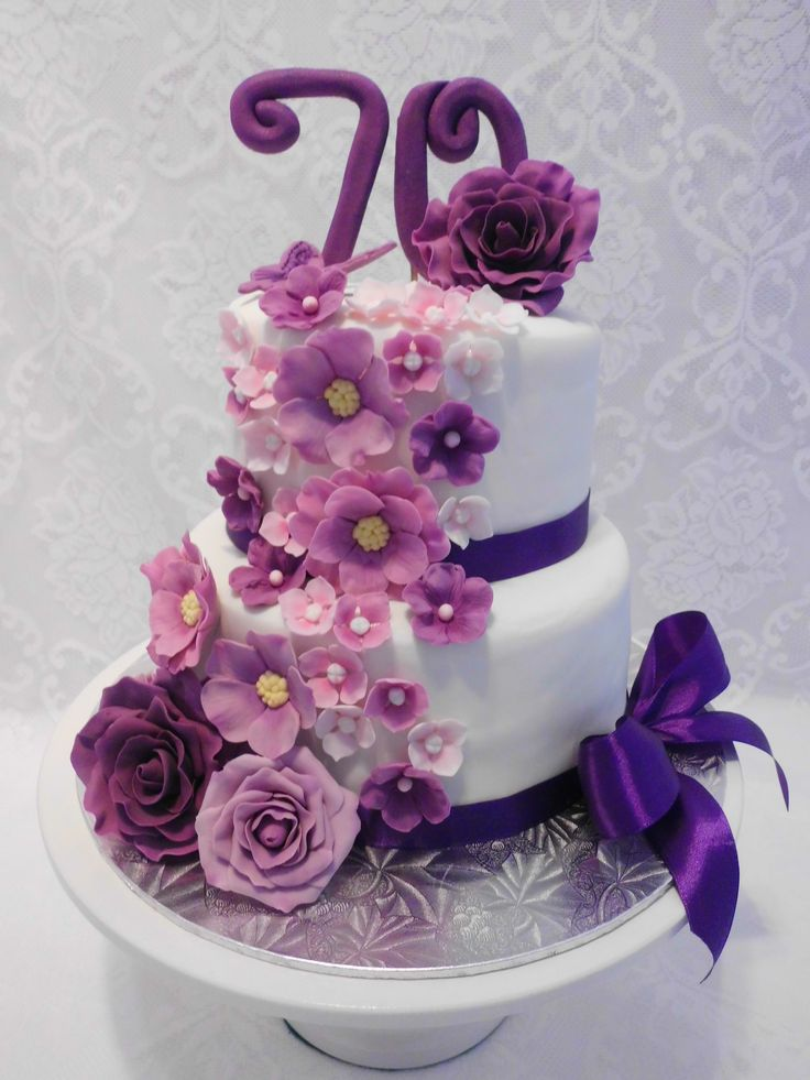 Floral Cascade in purple, pink & mauve  - 70th birthday cake for a lady who loves the colour purple. Fondant cake with gumpaste flowers and satin ribbon.