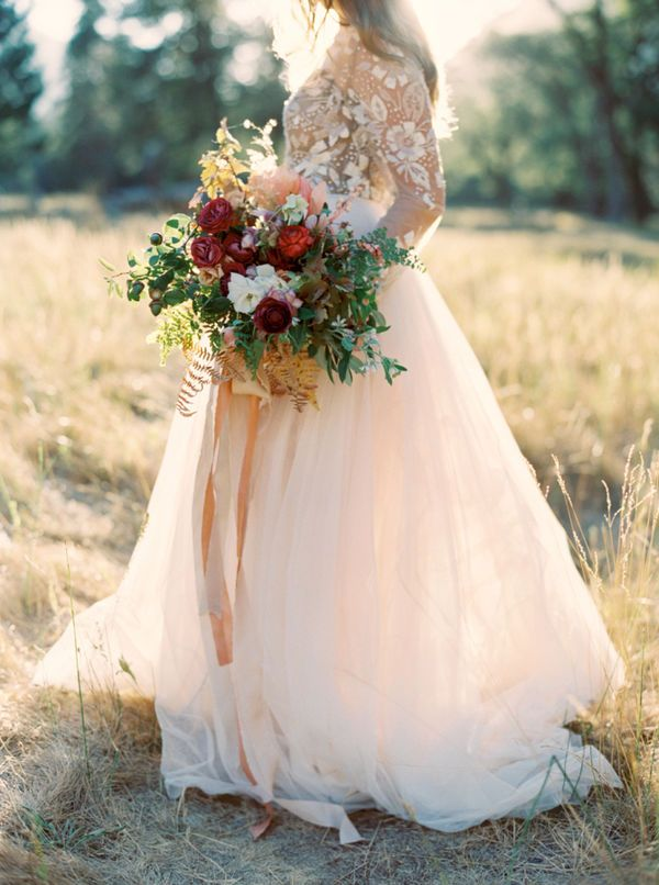 Blush lace long sleeve wedding dress: This beautiful hybrid of princess pouf and city girl sleek just glows in the evening sunlight. The long sleeves will keep your arms a little warmer and the blush will give you a wonderful foundation to your fall wedding color palette. It looks absolutely stunning with this red and blush fall wedding bouquet.