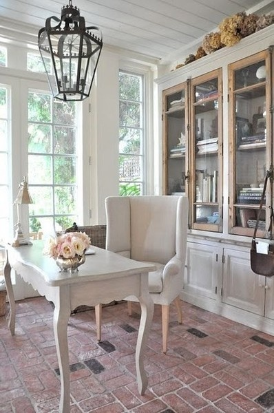 Brooke Giannetti's sunroom office, brick floor, neutral furniture, built-in bookcase cabinet