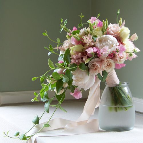 hand tied, cascade bridal bouquet containing peonies, sweet peas, astilbe, lisianthus, dahlias, Eos roses, Sweet Eskimo roses, White Mikado spray roses, and foliage cut from the garden