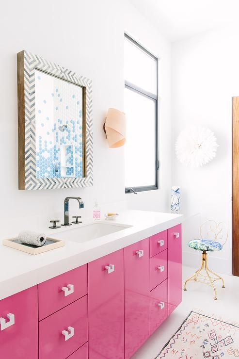 Contemporary pink bathroom features a black and white chevron mirror placed over an extra-wide pink bath vanity adorned with white hardware topped with white quartz fitted with a white porcelain sink and black modern faucet.