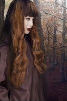 Langes gewelltes Haar mit rundem Pony und roten Highlights