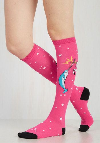 Delight in the dueling critters adorning your hot pink knee-highs! Floating amongst white stars and black trim, a narwhal and a unicorn go horn-to-horn in a humorous cosmic clash that you're proud to parade.