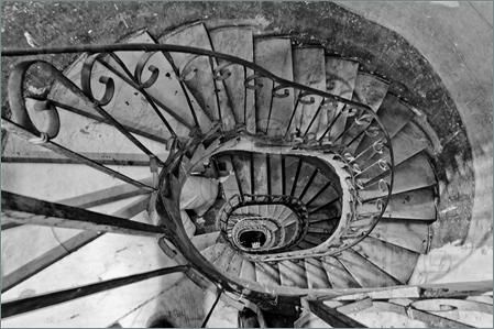 Pics of Looking down an old winding spiral stairs with a metal rail