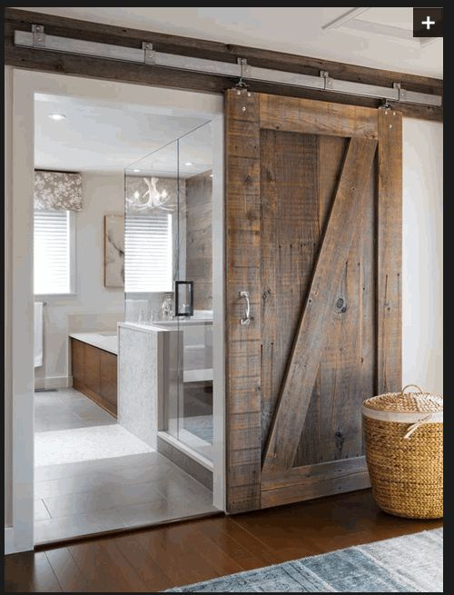 A rustic barn door with wood board above to anchor rail to