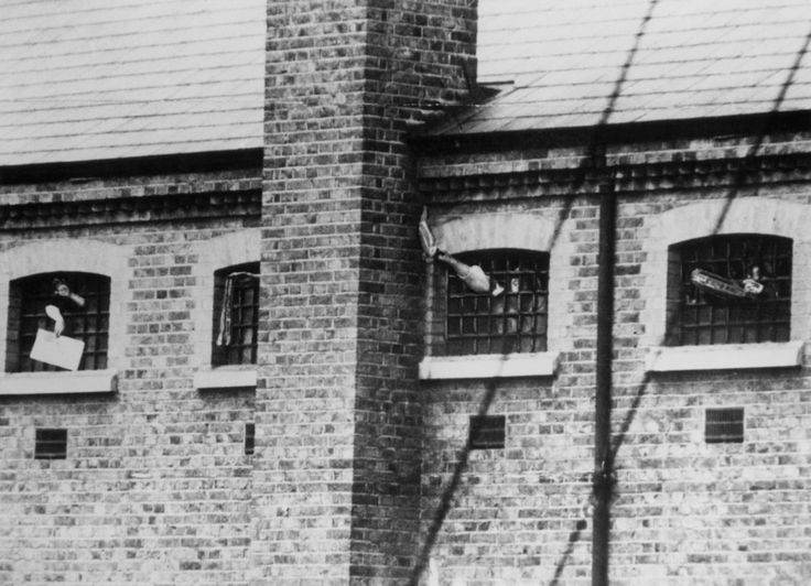 London, 1909: Imprisoned suffragettes waving through the windows of Holloway prison. | Feminist Photos From Around The World: Then And Now