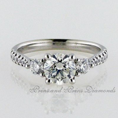 Centre stone is a 1.001ct J/SI1 round brilliant cut diamond in a trilogy setting with 2 smaller side stones and diamonds on the band equalling 0.45ct set in 18k white gold