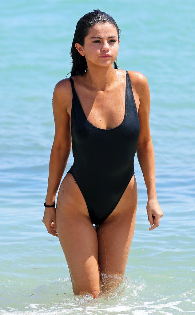 Damn! Gomez debuts some new hip tattoos in this swimsuit with thigh-high sides.