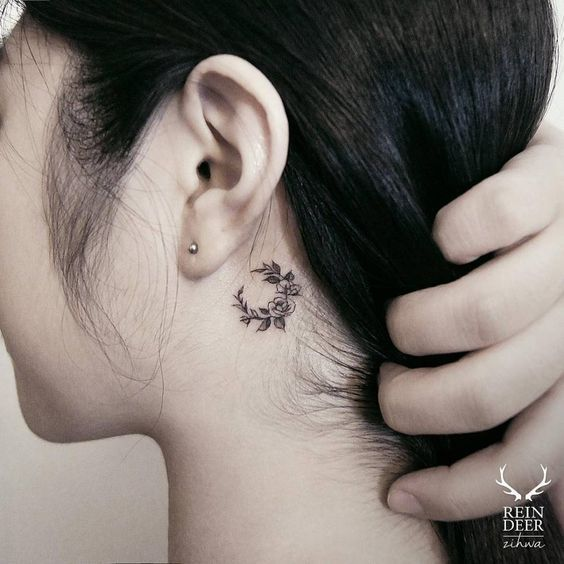 Small floral moon tattoo behind the left ear. Tattoo artist: Zihwa