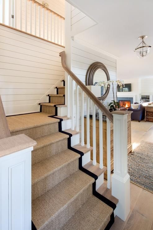 Cottage home with a white wood spindle staircase features a black bound sisal runner on gray wash wood stairs.