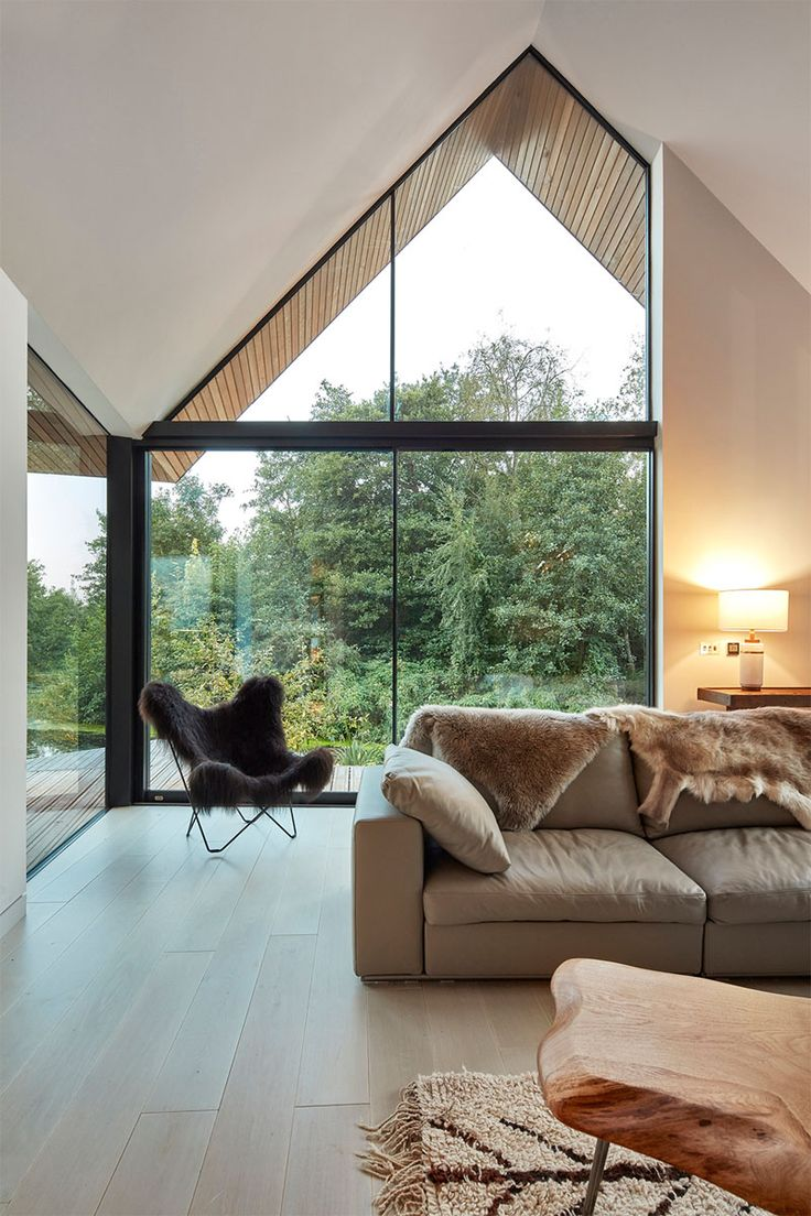 In This Double Height Modern Living Room Large Windows Follow The Roof Line And Provide