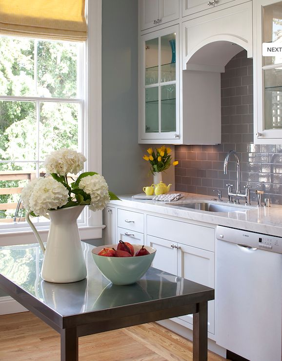 White & gray kitchen design with stainless steel kitchen island, creamy white kitchen cabinets, gray subway tiles, backsplash, marble counter tops, chrome hardware and faucet, oak floors and yellow geometric roman shade. blue gray walls paint color. white gray blue yellow kitchen colors.