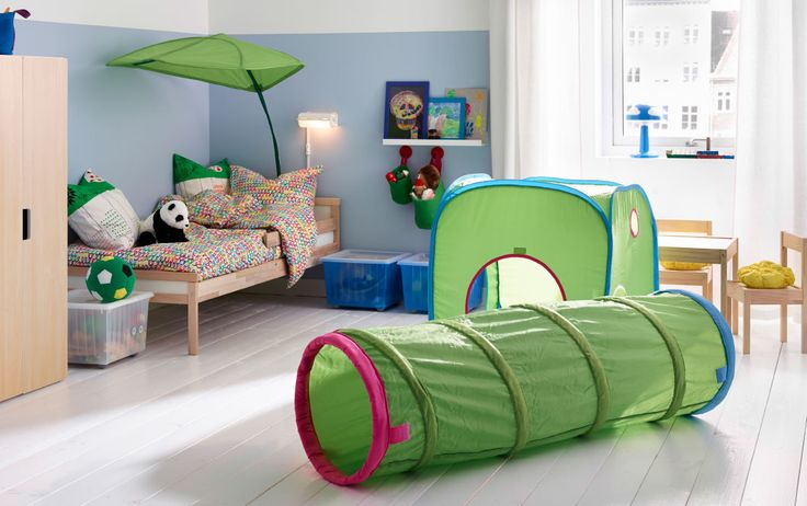 A colorful children's room with a bed in solid beech made with colourful quilt cover and pillowcase and with a green bed canopy that looks like a big leaf. Combined with a green pop-up playing tent and a tunnel.