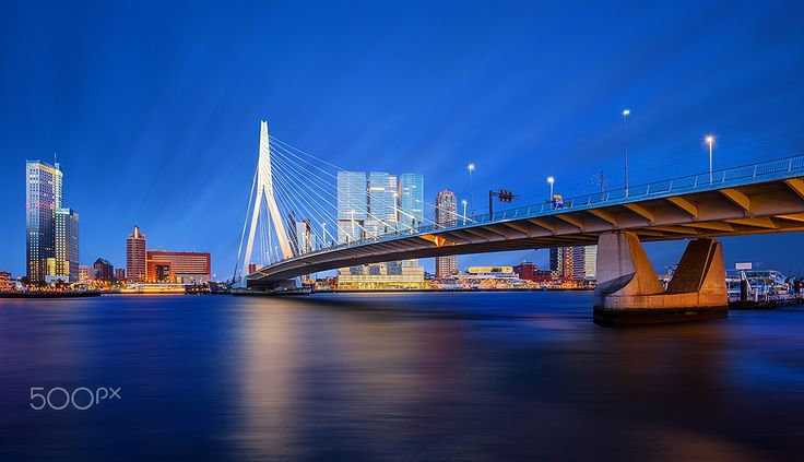 """Modern Rotterdam II - Rotterdam, the second-largest city in the Netherlands, is often called the """"Gateway to Europe"""", as it exploited its strategic location near the mouth of the Nieuwe Maas (New Meuse), a channel in the delta formed by the Rhine and Meuse rivers on the North Sea, and became one of the largest ports in the world. The 802-metre-long Erasmus Bridge is a cable-stayed bridge across the Nieuwe Maas designed by Ben van Berkel and completed in 1996. The 44-storey office skyscra..."""