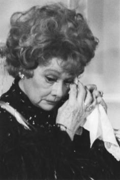 An emotional Lucille Ball reacts tearfully to a poignant salute to her and her longtime husband-collaborator, Desi Arnaz, by President Ronald Reagan on December 7, 1986 during a ceremony in the East Room of the White House in Washington for the Kennedy Center honorees.